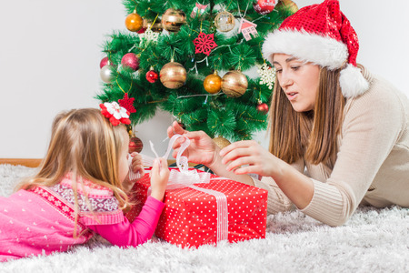 baby open present: Christmas Happy Family mother and her little daughter open Holidays Gift. Stock Photo