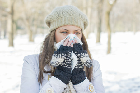 Young Woman in Winter Clothing  Blowing Nose with tissue paper outdoor Standard-Bild