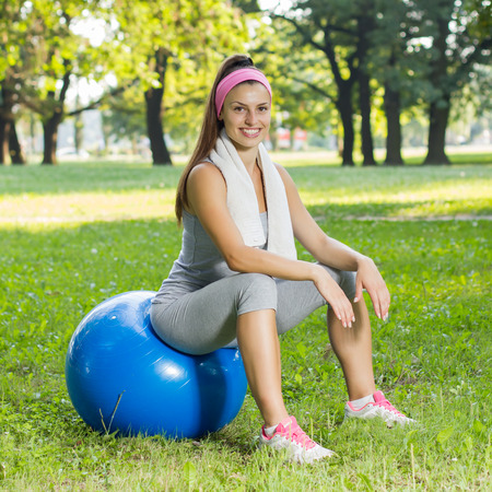 outdoor fitness: Fitness Healthy Smiling Young Woman resting on pilates ball at beautiful summer day in the park. Outdoor activity sporty lifestyle.