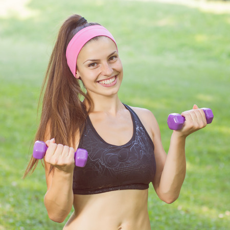 slim girl: Fitness Slim Woman Training with dumbbells. Smiling attractive female practicing using hand weights outdoor. Healthy lifestyle workout concept on beautiful summer day.
