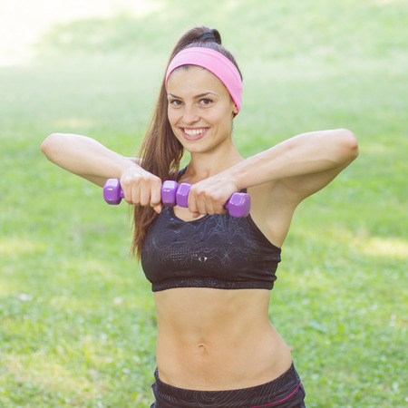 hand weights: Fitness Slim Woman Training with dumbbells. Smiling attractive female practicing using hand weights outdoor. Healthy lifestyle workout concept on beautiful summer day.