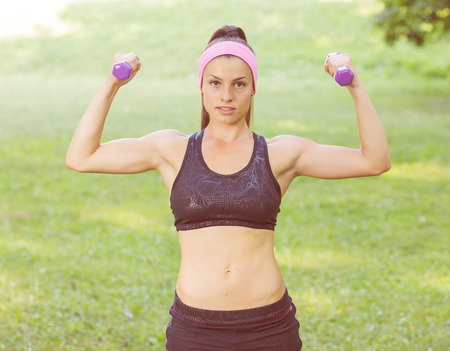hand weights: Fitness Slim Woman Training with dumbbells. Female practicing using hand weights outdoor. Healthy lifestyle workout concept on beautiful summer day. Stock Photo