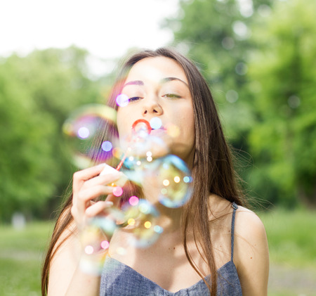 woman young: Young Woman Blowing Bubbles outdoor. Caucasian female Relaxing lifestyle in the park.