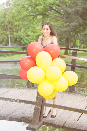 Happy, Beautiful, Carefree , Freedom Young Woman with Red and Yellow Balloons. Attractive caucasian female enjoying nature. photo