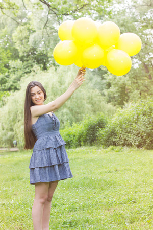 Happy, Freedom, Carefree Young Woman with Yellow Balloons at beautiful Summer Day Outdoor. Attractive female enjoying nature. photo
