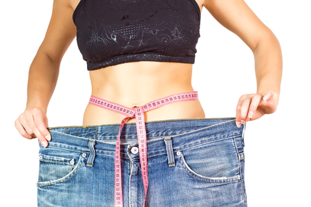 ideal: Slim Waist of Young Woman with perfect healthy thin body,showing her old jeans after successful diet. Unrecognizable person.Weight loss and slimming concept.