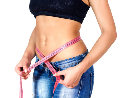 cinta metrica: Mujer delgada con el cuerpo perfecto de buena condición física, que mide su cintura fina con una cinta métrica.