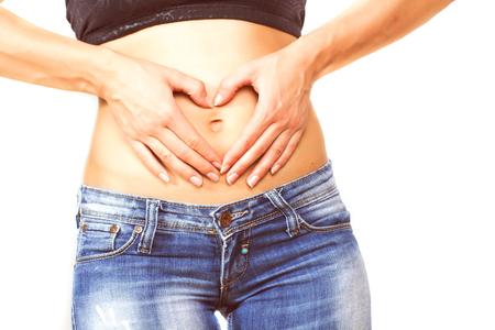 vientre femenino: Delgado cuerpo femenino con perfecto ajuste de la cintura saludable, mujer de las manos que forman el corazón con la mano sobre el vientre.