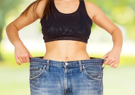 cintura: Medida de la cintura delgada de la mujer joven con perfecto cuerpo delgado sano, mostrando sus pantalones vaqueros viejos después de la dieta con éxito sobre el fondo de la naturaleza. Foto de archivo