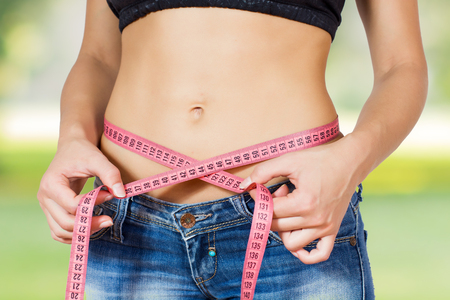 losing weight: Slim Female with perfect healthy fitness body, measuring her thin waist with a tape measure.  Stock Photo