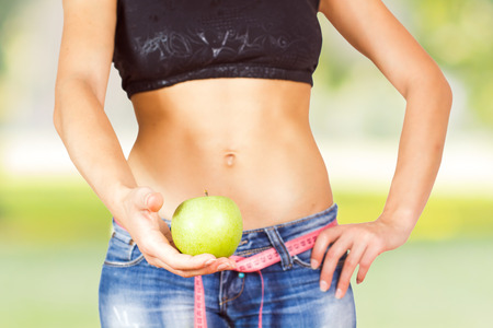Slim Female with perfect healthy fit body, showing green apple .  Caucasian young woman in jeans. Unrecognizable person.Diet and weight loss concept.