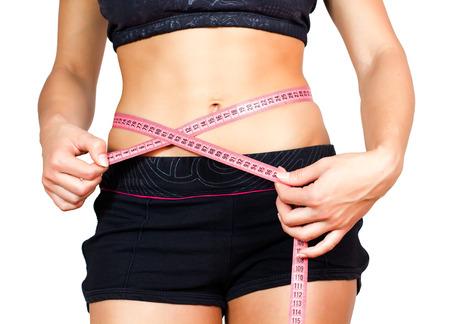 cintura perfecta: Mujer delgada con el cuerpo perfecto de buena condición física, que mide su cintura fina con una cinta métrica.