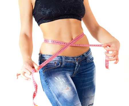 cintura perfecta: Slim Female with perfect healthy fitness body, measuring her thin waist with a tape measure.  Foto de archivo