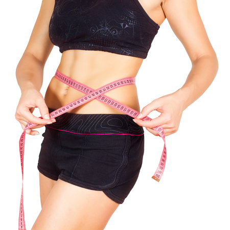 are slim: Slim Female with perfect healthy fitness body, measuring her thin waist with a tape measure. Stock Photo