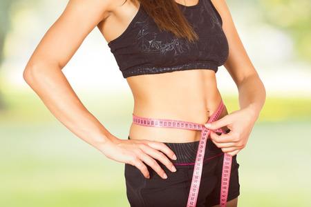 cintura: Mujer delgada con el cuerpo perfecto de buena condición física, medición de la cintura delgada con una cinta métrica.