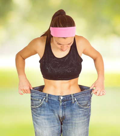 slim tummy: Slim Waist of Young Woman with perfect healthy thin body,showing her old jeans after successful diet. .Weight loss and slimming concept. Stock Photo