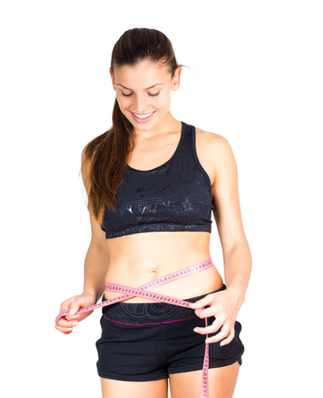 cintura perfecta: Slim Young Woman with perfect healthy fitness body, measuring her thin waist with a tape measure.