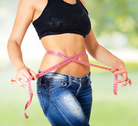 cintura perfecta: Slim Female with perfect healthy fitness body, measuring her thin waist with a tape measure .