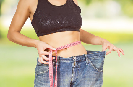 Slim Female with perfect healthy fitness body, measuring her thin waist with a tape measure .
