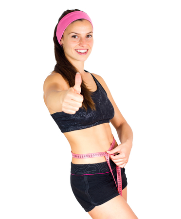 Slim Young Woman with perfect healthy fitness body, measuring her thin waist with a tape measure.