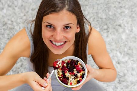 comiendo cereal: Mujer joven feliz comiendo cereales muesli con frutas en un tazón en el hogar. Alimentación saludable y el concepto de dieta. Foto de archivo