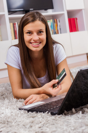 over paying: Shopping Online. Beautiful and smile young woman with credit card paying over internet at home.