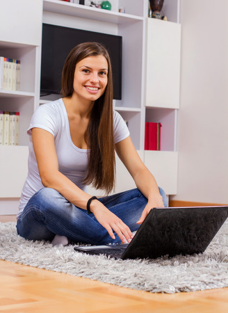 casual wear: Young beautiful woman, browsing internet, using laptop computer,in casual wear, on floor at home.