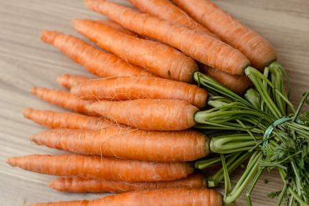 ?  ? carrot: Fresco zanahorias Manojo sobre fondo de madera. Foto de archivo