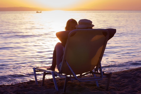 Woman and little girl sitting on sunbeds and relaxing on the beach at sunset.