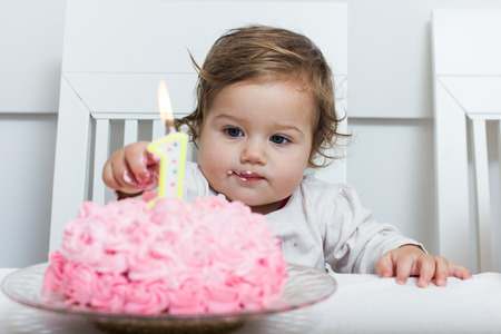 Celebrating First Birthday , portrait of cute little girl with cake. Stock Photo
