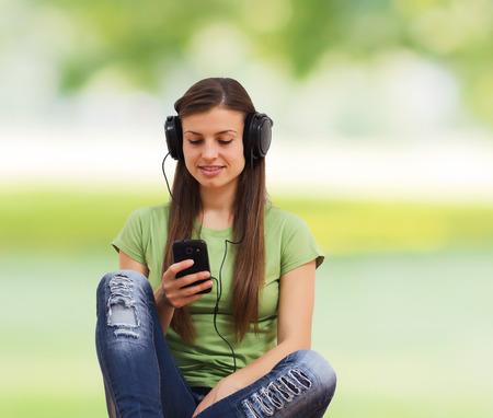 listening to music: mujer joven hermosa que escucha la música y que usa el teléfono móvil.