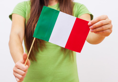 nationalistic: Closeup of female hands holding Italian flag. Stock Photo