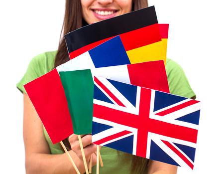 languages: Femenino Estudiante sosteniendo banderas internacionales. Apoyo o el concepto de la escuela de idiomas. Foto de archivo