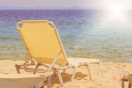 sunbeds: Holiday, Travel and Vacation concept with Sunbeds on the Sandy Beach near the Aegean Sea at beautiful summer day. Stock Photo