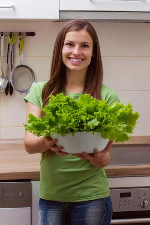 légumes verts: Jeune laitue tenant femme, salade verte dans la cuisine