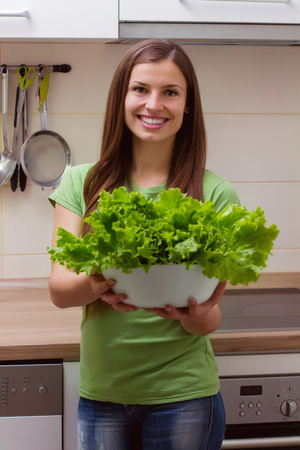 vegetales verdes: Young woman holding lettuce, green salad in the kitchen Foto de archivo