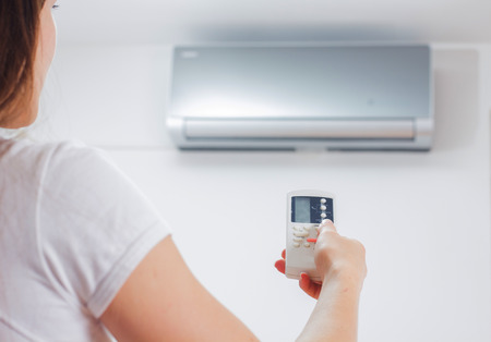 Air Conditioner , woman hand with remote control, adjustment temperature,at home