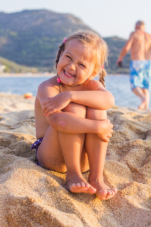 little  girls: Smiling Little Girl ,sitting on the sandy beach, looking at the camera.