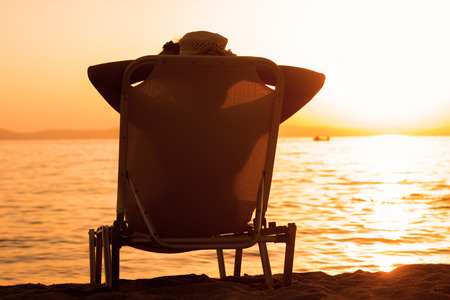 relaxing beach: Silhouette of woman with hat , sitting on sunbeds at beach, enjoying sunset. Summertime lifestyle relaxing. Stock Photo