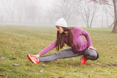 estiramiento: Mujer ajustada, haciendo ejercicios de estiramiento, el concepto de estilo de vida saludable, actividades al aire libre, la temporada de invierno