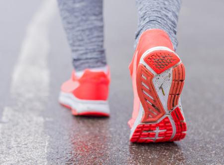 activ: Sporty Runner feet running on the wet road. Stock Photo