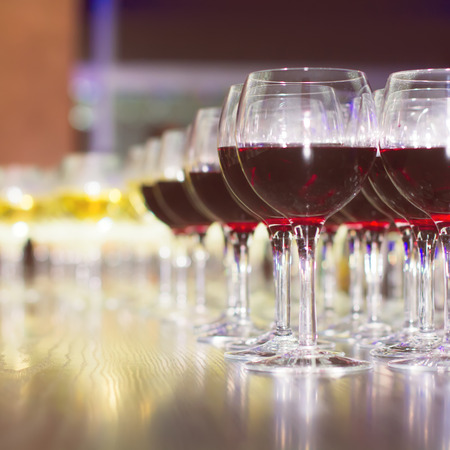 consuming: Wineglasses with red wine in row on the bar, ready for consuming on event.