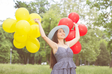 Happy Beautiful Carefree Young Woman with Red and Yellow Balloons. Attractive caucasian female enjoying nature. photo