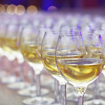 consuming: Wineglasses with white wine in row on the bar, ready for consuming on event.