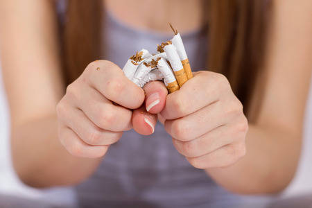 Quit Smoking, woman hands breaking bunch of cigarette. Stock Photo