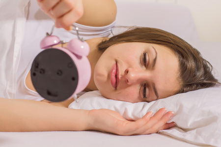 asleep: Young woman looking in the alarm clock in the bed.