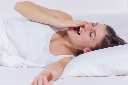 Waking up, young woman yawning and stretching in the bed.
