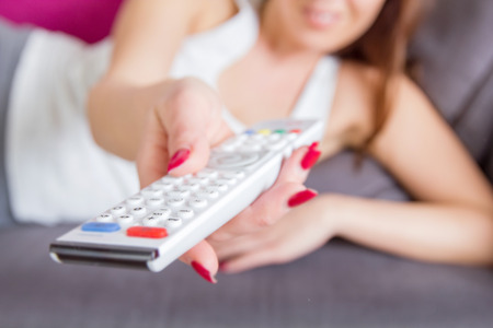 unrecognizable person: Television remote control in woman hand. Unrecognizable person. Stock Photo