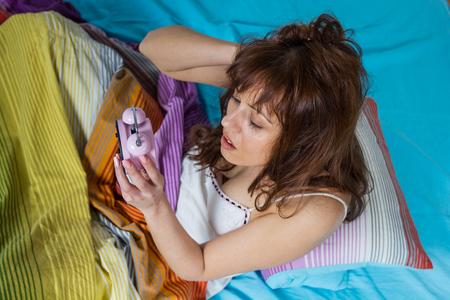 overslept: Oversleeping woman looking on the alarm clock.
