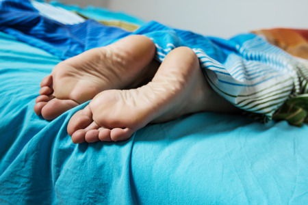 Woman feet on the bed. Relax and sleeping lifestyle.